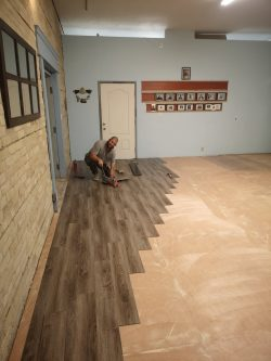 Photo shows Ark Aid male Volunteer Installs the New Beckham Brothers Reading Loose Caboose Luxury Vinyl Planks on sanded sub floor. Room has blue walls and Ark Aid memorabilia decorations on the walls.